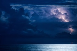 Massive cumulus clouds and lightning at night over the Black sea
