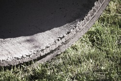 Massive gray concrete ring with shadow lays on a grass, abstract industrial photo background