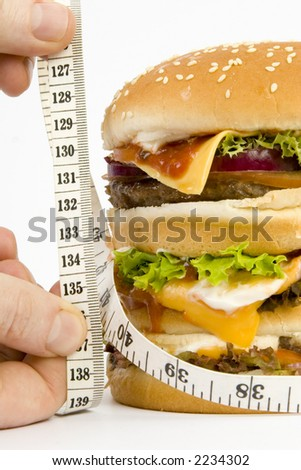 "Massive Hamburger, isolated on white - cheese, tomato, lettuce, 3 burgers, loads of bread.. On weighting scales with the woed ""fat"". tape measure to illustrate unhealthy/ fat eating. With tape measure"