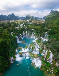 Massive hidden waterfall surrounded by mountain with blue clean water. Paradise on the border between China and Vietnam. Ban gioc waterfall, Detian.