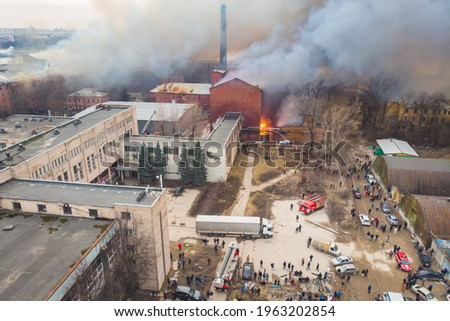 Massive large blaze fire in the city, aerial drone top view brick factory building on fire, hell major fire explosion flame blast,  with firefighters team, arson, burning damage destruction  Stock photo ©