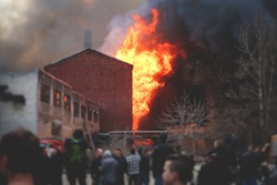 Massive large blaze fire in the city, brick factory building on fire, hell major fire explosion flame blast,  with firefighters team firemen on duty, arson, burning house damage destruction