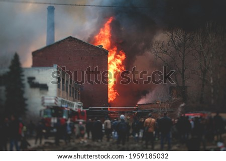 Massive large blaze fire in the city, brick factory building on fire, hell major fire explosion flame blast,  with firefighters team firemen on duty, arson, burning house damage destruction  Stock photo ©