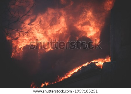 Massive large blaze fire in the city, brick factory building on fire, hell major fire explosion flame blast,  with firefighters team firemen on duty, arson, burning house damage destruction  stock photo
