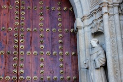 Massive large brown red wooden church doors. They are in the town of Toledo. You can see a wall with stones, a statue and different decorations. The photo shot has a vintage and typical catholic taste