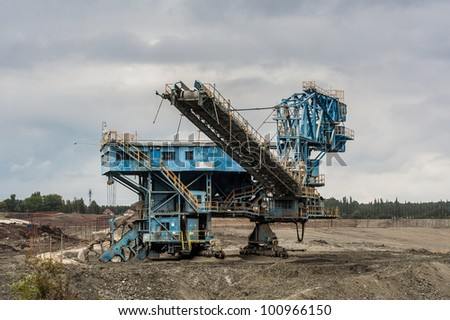 massive machine for coal mining in desolated landscape in cloudy day