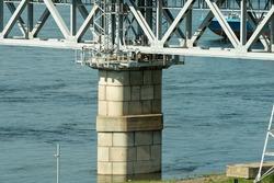 Massive pillars of a railway bridge with a columnar superstructure. Railway bridge with arches from profile metal rolling. Railway bridge over the river.