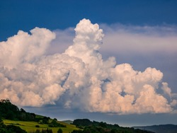 Massive rain clouds - Cumulonimbus - forming in the blue sky over hilly landscape