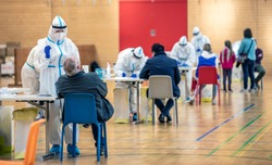 Massive rapid COVID-19 testing for the  popolation. Health workers in protective suits are engaged in salivary and nasal tests inside a public gym. People get tested against the Coronavirus.