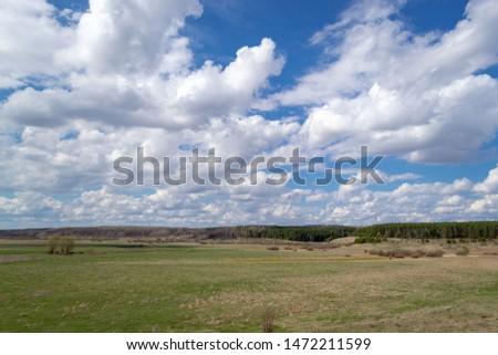 Massive white cumulus clouds in a blue sky over a green plain. #1472211599