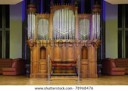 Massive wooden pipe organ with many metal pipes and ornate finishing