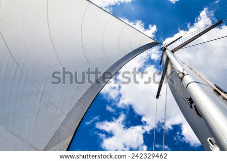 Mast and sail against the sky with clouds. Mast and sail against the sky with clouds on a sunny day. Bottom view.