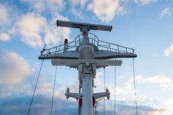 Mast of a cargo ship with navigation equipment bottom view. Radar, signal beeps and signal lights.