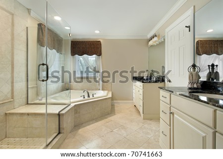 Master bath with cream colored cabinetry and glass shower - stock photo