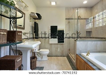 Master bath with glass shower tub with oak wood cabinetry