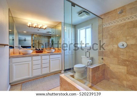 Master bathroom interior with walk in shower and white vanity cabinet with two bowl sinks. Northwest, USA