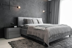 Master bedroom for a lonely stylish man, a bachelor. Modern room with trendy gray interiors, large king-size and stylish lamps.