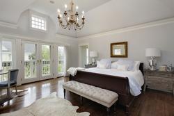 Master bedroom in luxury home with doors to balcony.