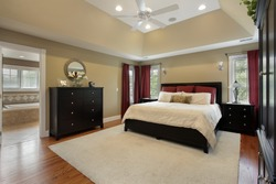 Master bedroom in luxury home with view into bathroom