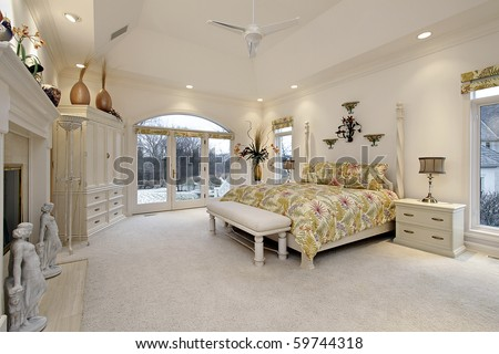 Master bedroom in luxury home with white fireplace