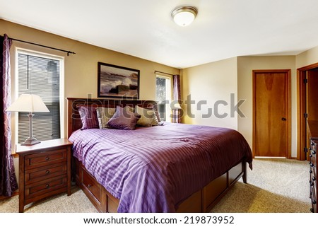 Master bedroom interior. Rich furniture set with bright purple bedding and pillows