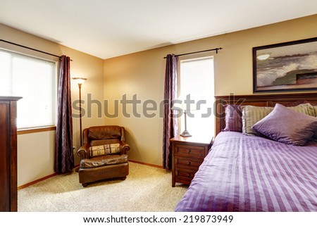 Master bedroom interior. Rich furniture set with bright purple bedding and pillows. Leather armchair in the corner