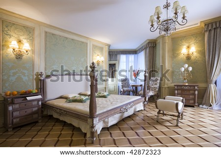 Master bedroom with beautiful bed and linens and sitting area by the