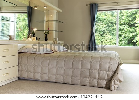 Master bedroom with king size bed, large mirror and open curtains showing green trees in background