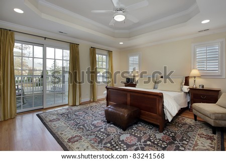 Master bedroom with tray ceiling and deck view. Master Bedroom With Tray Ceiling And Deck View Stock Photo