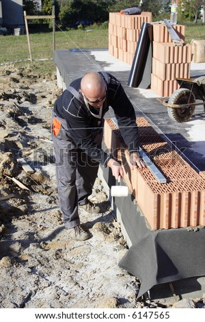 master bricklayer building-up one family house - stock photo