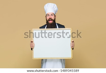 Master cook giving cooking class. Bearded man cook or chef holds empty board in cooking school. Chef teaching master class. Handsome cook holds blank board. Place for text. Restaurant or cafe menu.