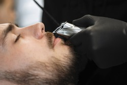 Master cuts and trimming a mustache for the beard guy with a hair clipper in a hairdressing chair in a barbershop salon. Selective focus, blurred background.