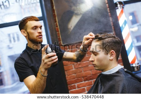 Master cuts hair of men in the barbershop, hairdresser makes hairstyle for a young man #538470448