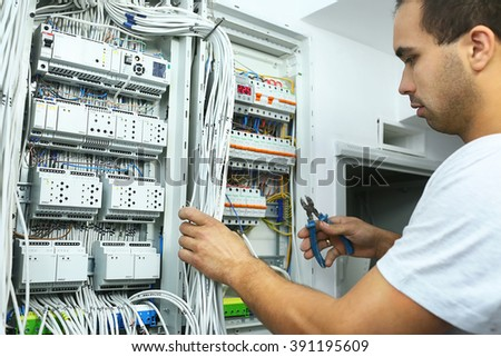 Master electrician at work near the plate with a plurality of wires. Repairs in the house or apartment, wiring electricity #391195609