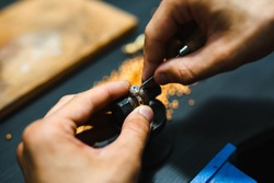 Master goldsmith while working on jewelry on the of work table.
