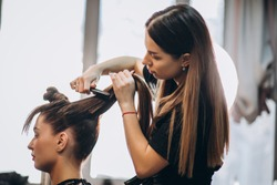 Master hairdresser makes hair style girl with hairdryer and hair care products