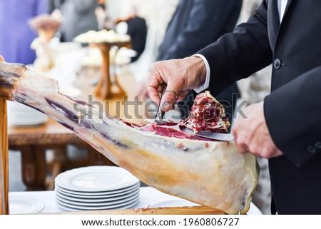 master ham cutter. professional cutting slices of Iberian ham.typical Spanish tapa, acorn-fed ham Foto stock ©