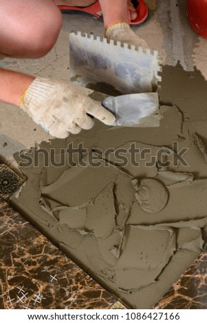 Master husband presses a spatula glutinous solution to the cement surface #1086427166