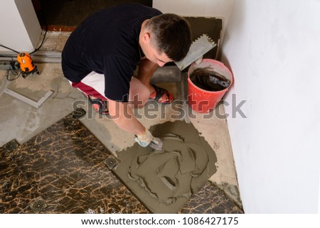 Master husband presses a spatula glutinous solution to the cement surface #1086427175