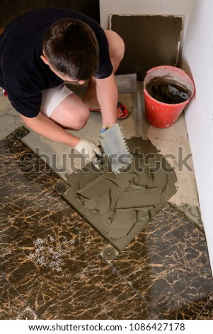 Master husband presses a spatula glutinous solution to the cement surface #1086427178