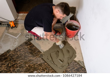 Master husband presses a spatula glutinous solution to the cement surface #1086427184