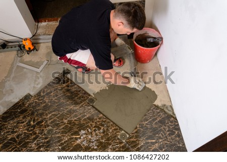 Master husband presses a spatula glutinous solution to the cement surface #1086427202