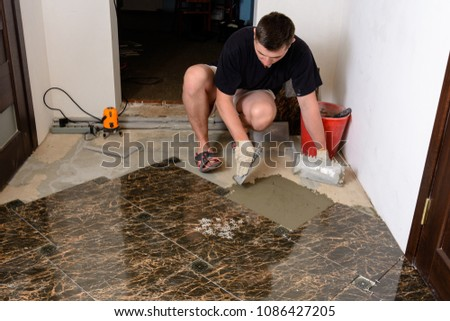 Master husband presses a spatula glutinous solution to the cement surface #1086427205