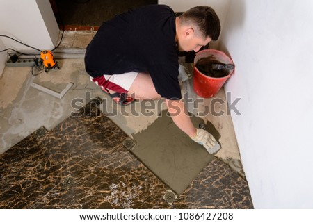 Master husband presses a spatula glutinous solution to the cement surface #1086427208