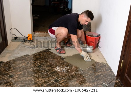 Master husband presses a spatula glutinous solution to the cement surface #1086427211