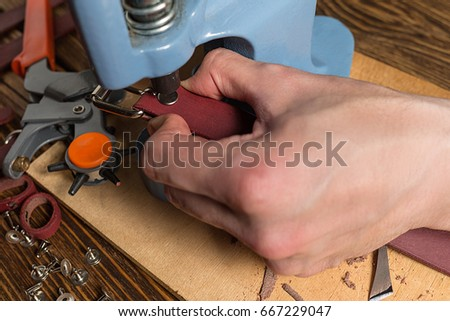 Master is working on press with skin. On brown wooden table scattered with tools and accessories. Photo. #667229047