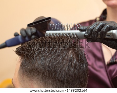 Master making hairstyling with round comb and hair dryer, close up view. Stylists hands in black rubber gloves. Hairdresser at work in barbershop. Selective soft focus. Blurred background