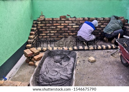 Master masons start masonry and check that it is horizontal.
