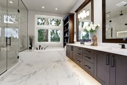 Master modern bathroom interior in luxury home with dark hardwood cabinets, white tub and glass door shower