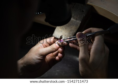 master of jewelry manually inserts gems into the frame of future jewelry. Working desk for craft jewelery making with professional tools. Sapphire diamond ring on the jeweler's desktop
